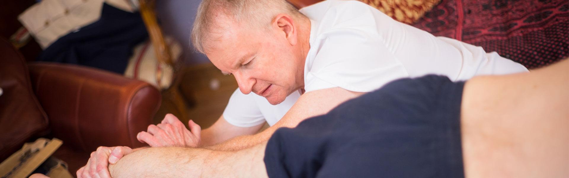 Slider image showing curative massage to leg
